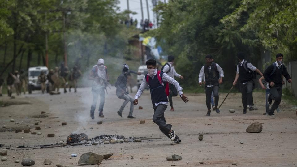 Kashmiri students run for cover as they are chased by policemen during a protest in Budgam on Wednesday.