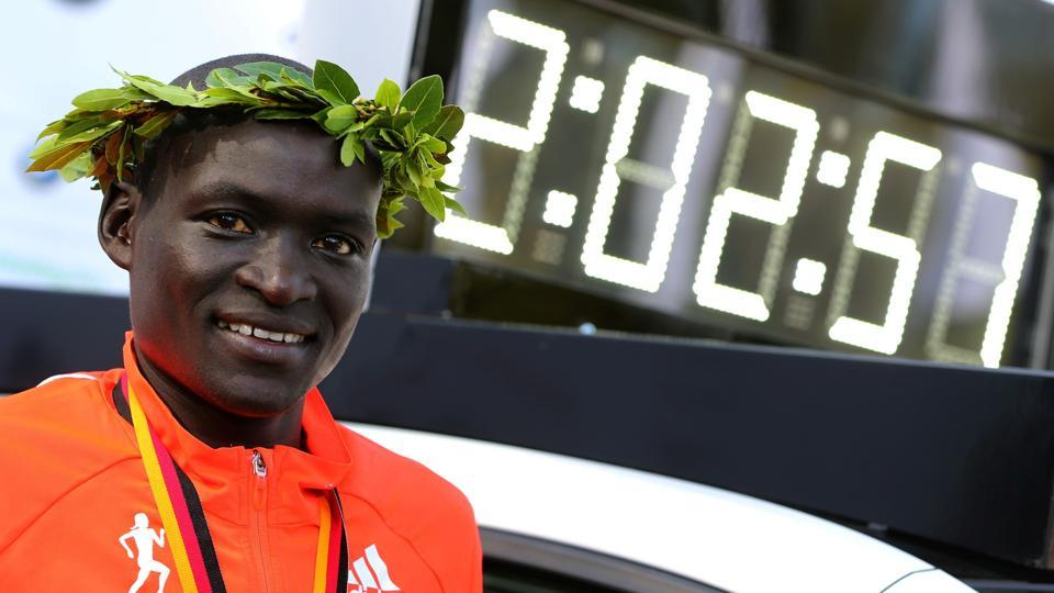 Kenya's Dennis Kimetto poses next to the vehicle displaying his new world record at the awards ceremony for the 2014 Berlin marathon. New rules planned by athletics chiefs to combat doping in athletics may see only records set in specific competitions ratified in the future.