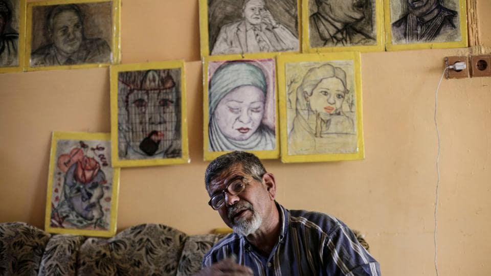 Iraqi painter Mustafa al-Taee sit in front of a display of his art work as he speaks to The Associated Press, at his home in the northern town of Hamam al-Alil, near Mosul, Iraq.