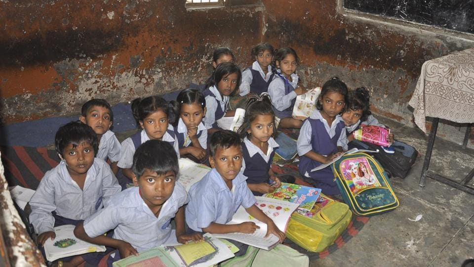 Students sit on torn, rugged mats at Government Primary School, Mauli Jagran.