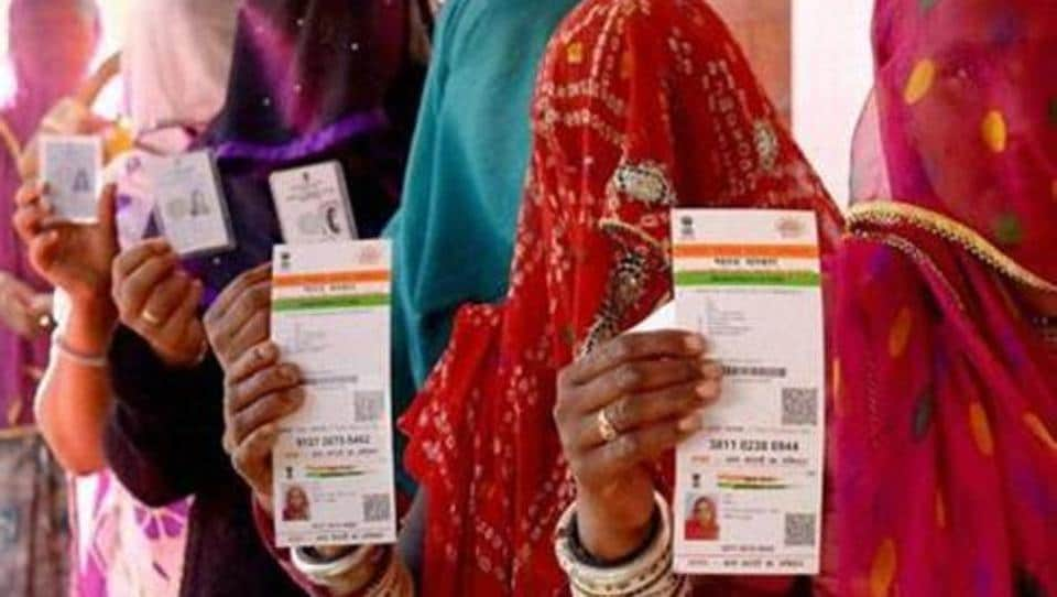 Rajasthani women show their Aadhaar cards while standing in a queue to vote in the Ajmer District Panchayat elections.