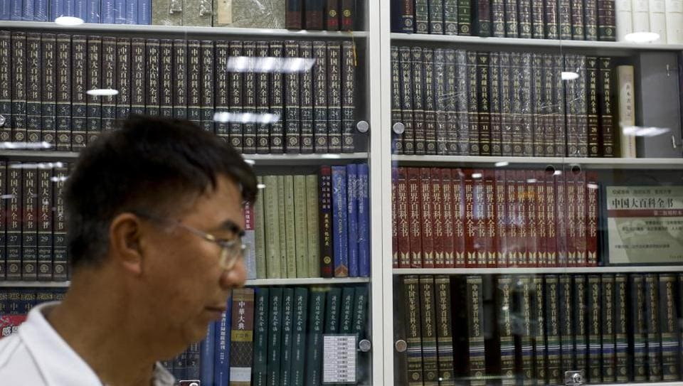 A Chinese man walks by a cabinets displaying Chinese encyclopedias at a book store in Beijing on Thursday.