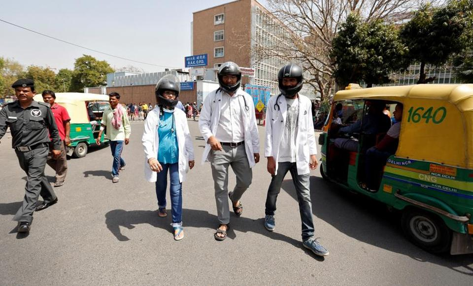 Doctors wear crash helmets outside the All India Institute Of Medical Sciences (AIIMS) during a protest to highlight the lack of security offered to doctors, in New Delhi, March 23