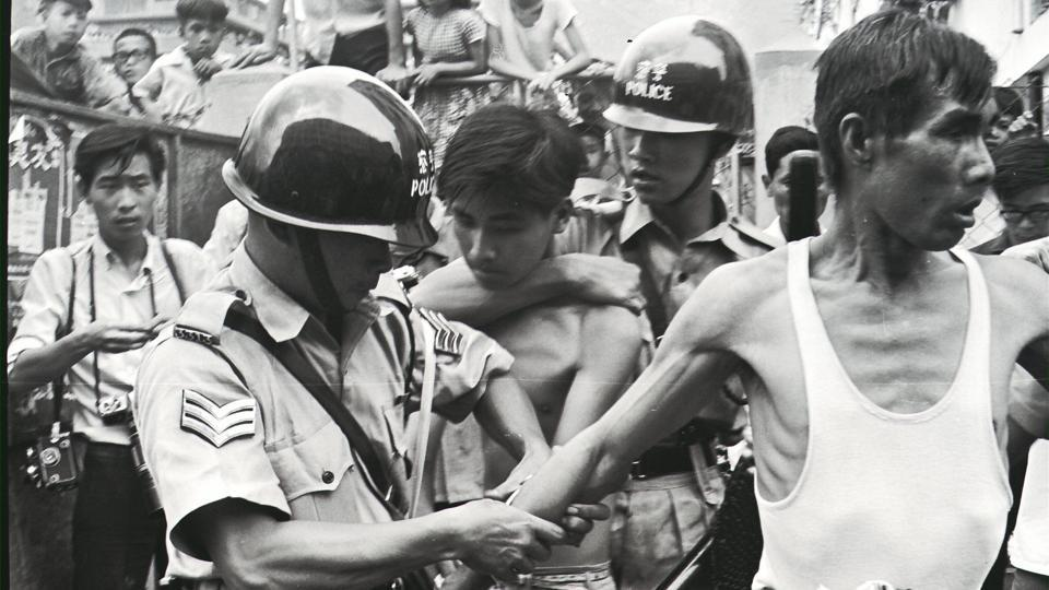In this photograph received from the South China Morning Post archive on May 2, 2017 and taken on May 12, 1967, police arrest two left-wing demonstrators during a clash in San Po Kong in Hong Kong. Hong Kong is unrecognisable now from the city which 50 years ago was the scene of bloody riots, fuelled by resentment of colonial rule and inspired by the Cultural Revolution unfolding in China.