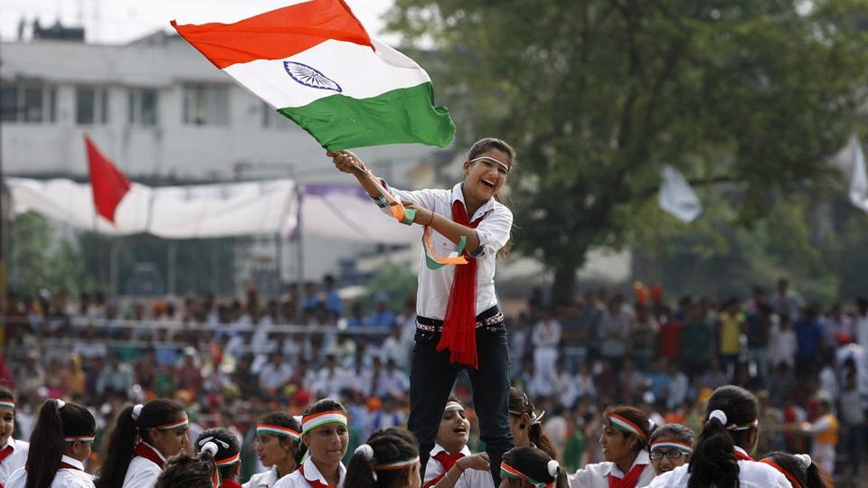 A school girls waves the Indian national flag as she performs on the occasion of 69th anniversary of India's independence from British rule, in Jammu, India, Saturday, Aug. 15, 2015.
