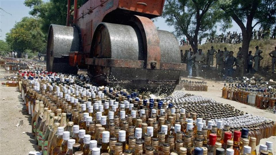 A roller crushes liquor bottles at Koba village, about 18 km (12 miles) north from Ahmedabad, in this file photo from 2006.