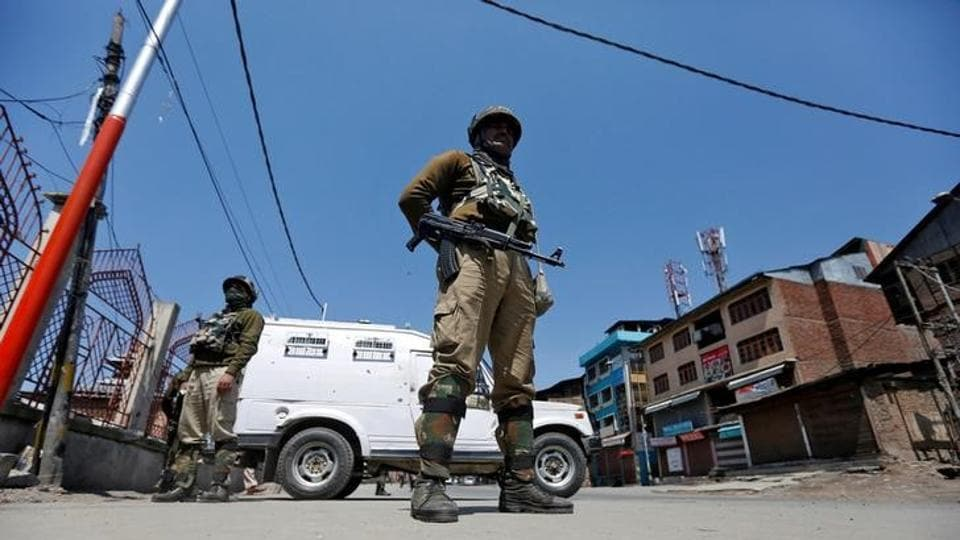 Security personnel guard a deserted street in downtown Srinagar.