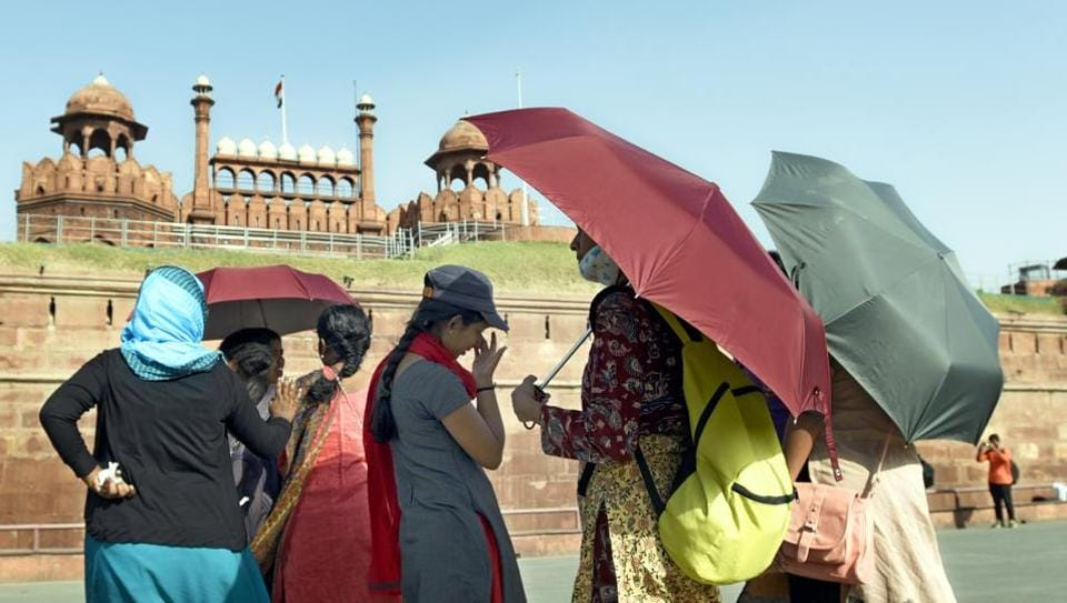 Tourists cover themselves with caps and umbrellas during an extremely hot day in Delhi.