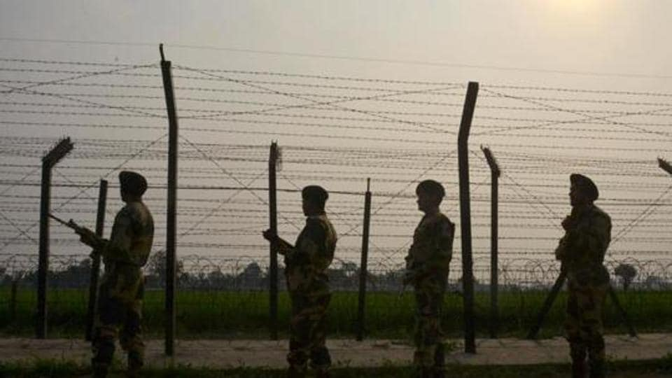 Security personnel patrolling along a fence at the India-Pakistan border, at Wagah.