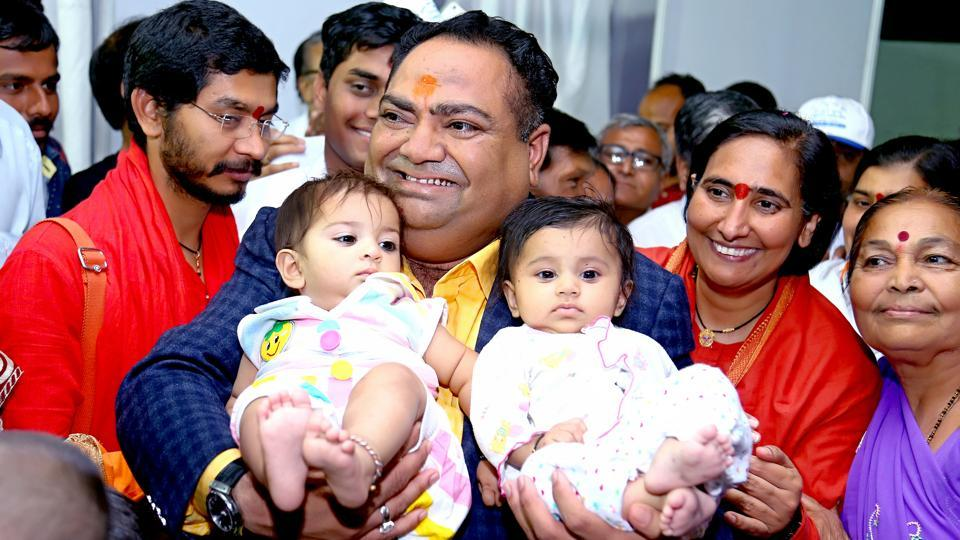Lavji Daliya, a Surat-based realtor, holds two babies at an event.
