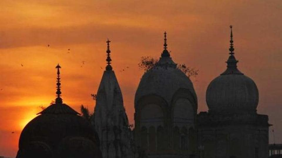 Birds fly at sunset over a temple in India.