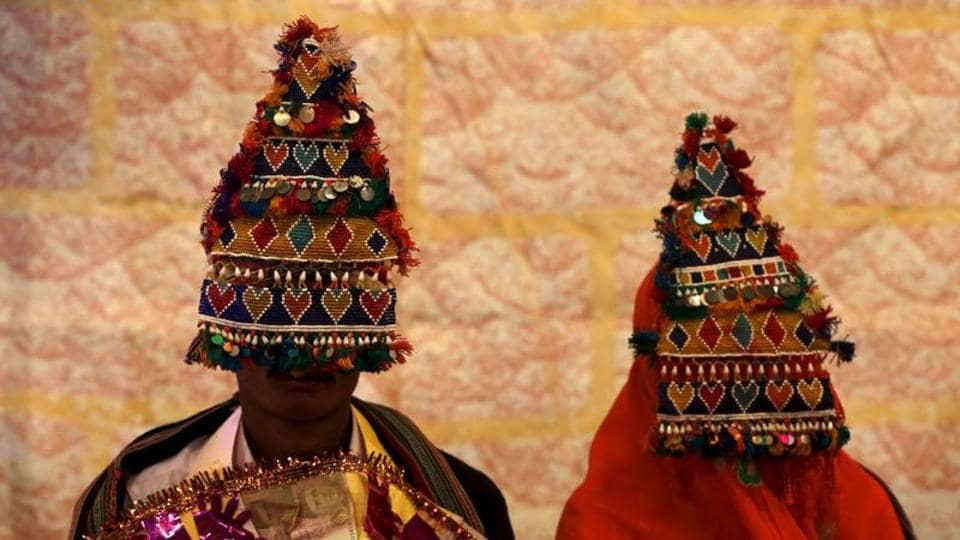 A bride and groom in traditional garlands wait for their wedding to start in Karachi, Pakistan, in January 2016.