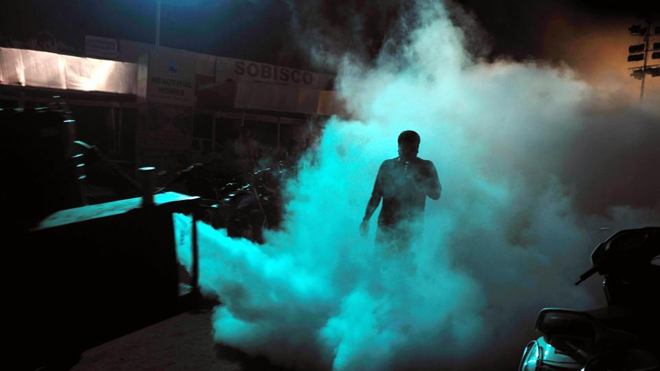 Municipal corporation workers pump mosquito repellent to control mosquito menace.