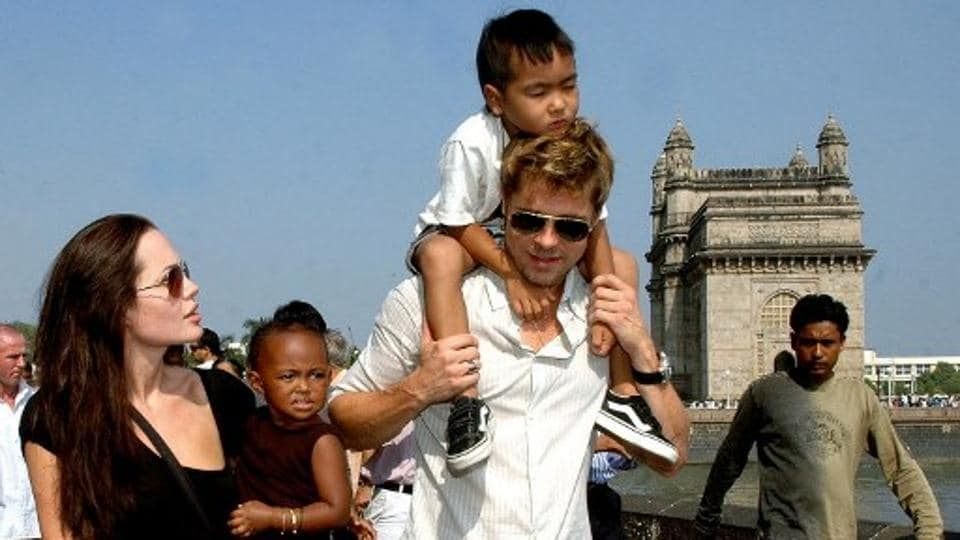 Angelina Jolie (L) holds daughter Zahara as husband and actor Brad Pitt (C) carries son Maddox during a stroll on the seafront promenade at the historic Gateway of India, (R) outside their hotel in Mumbai, 12 November 2006.