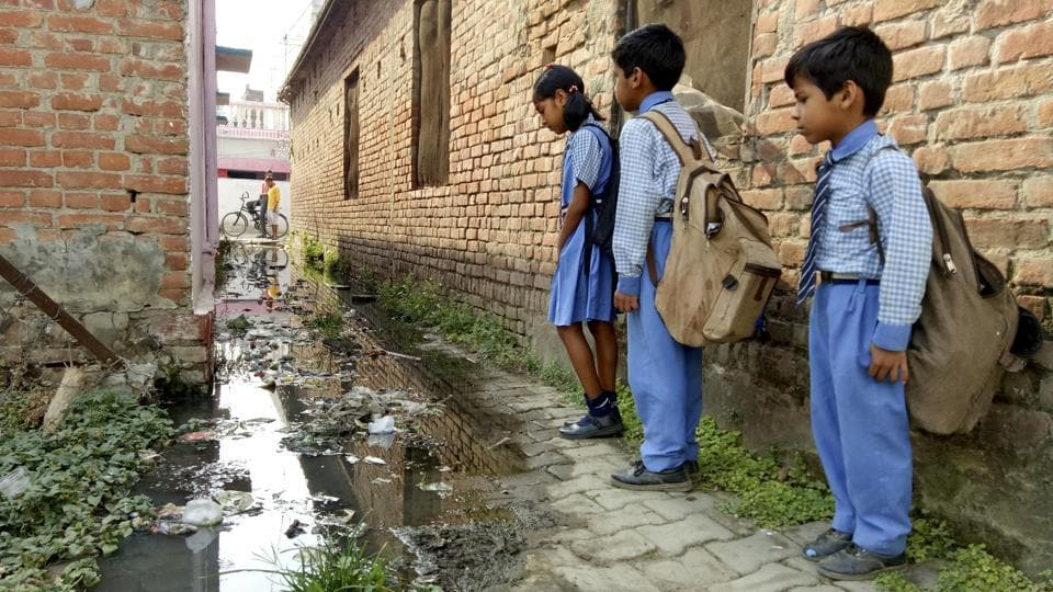 School children walk beside overflowing sewerage water through narrow streets of Uttar Pradesh's Gonda, which has been declared as the dirtiest city in the country.