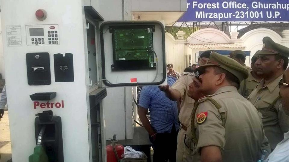 Police officers checking a petrol pump machine in Mirzapur, Uttar Pradesh, May 1.  The way technology was being used to pilfer petrol and diesel in the state makes it clear that the rights of the average consumer are not safe anywhere.