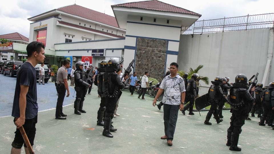 A villager (L) living near the prison and anti-riot policemen with rifle guard in front of Sialang Bungkuk jail after about 200 prisoners broke out of jail in Pekanbaru on Indonesia's Sumatra island, May 5, 2017.