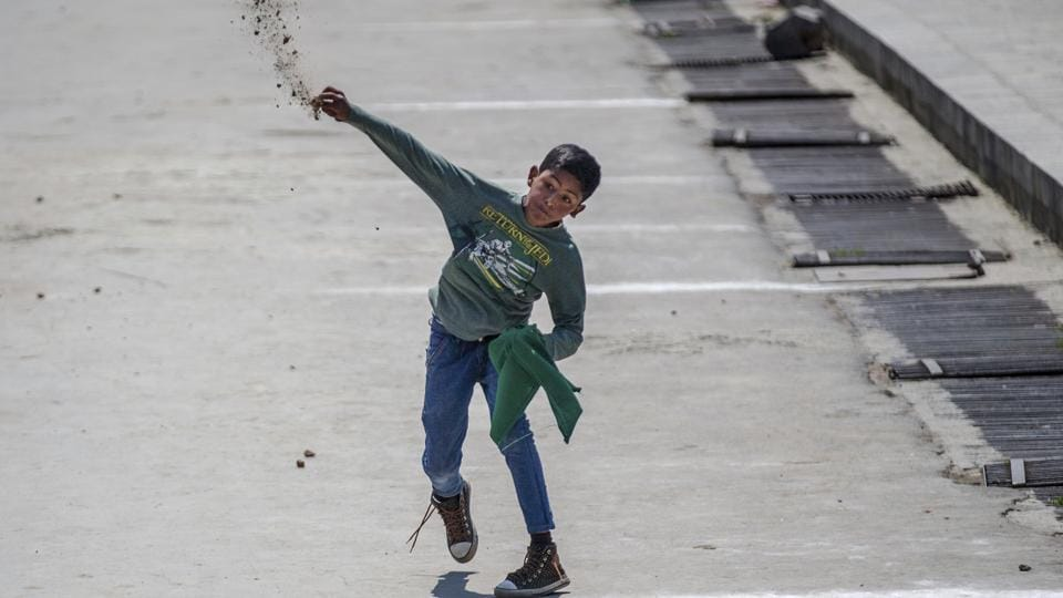 A young Kashmiri protester throws stones at government forces during a protest in Srinagar,  Jammu and Kashmir, Friday, May 5, 2017.