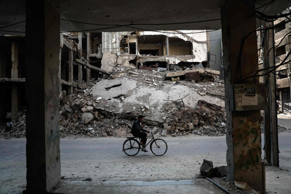 A Syrian man rides a bicycle past destroyed buildings in the rebel-held town of Douma.