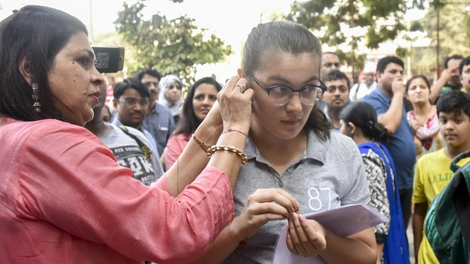 A student gets her earrings removed before entering the examination hall to take the NEET on Sunday.