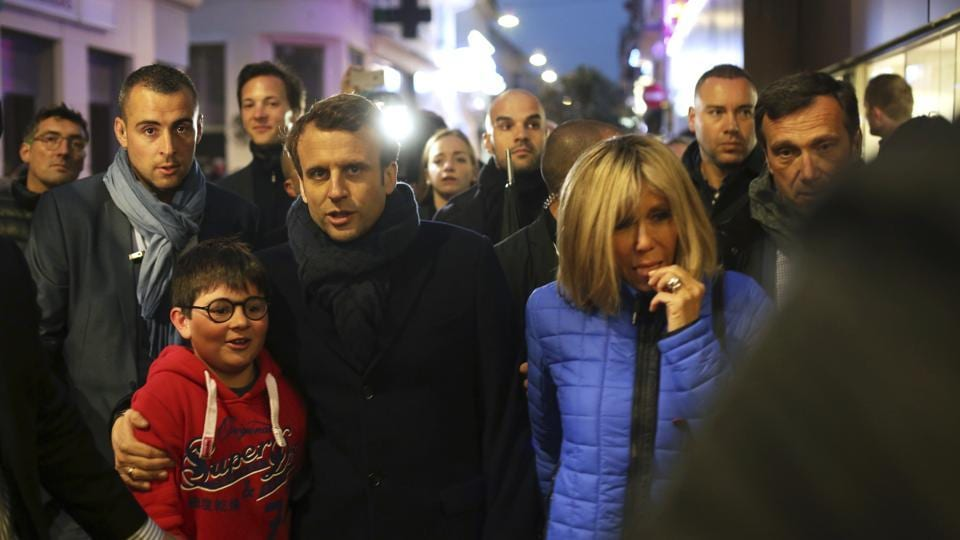 French independent centrist presidential candidate, Emmanuel Macron and his wife Brigitte walk in a street of Le Touquet, northern France on Saturday.