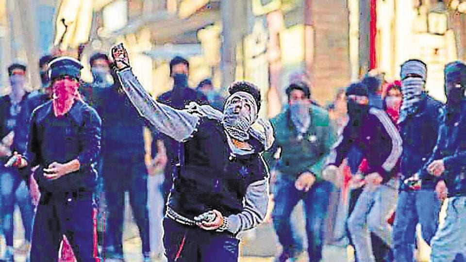 Masked Kashmiri youth throw stones at security forces during a protest in Srinagar in February.