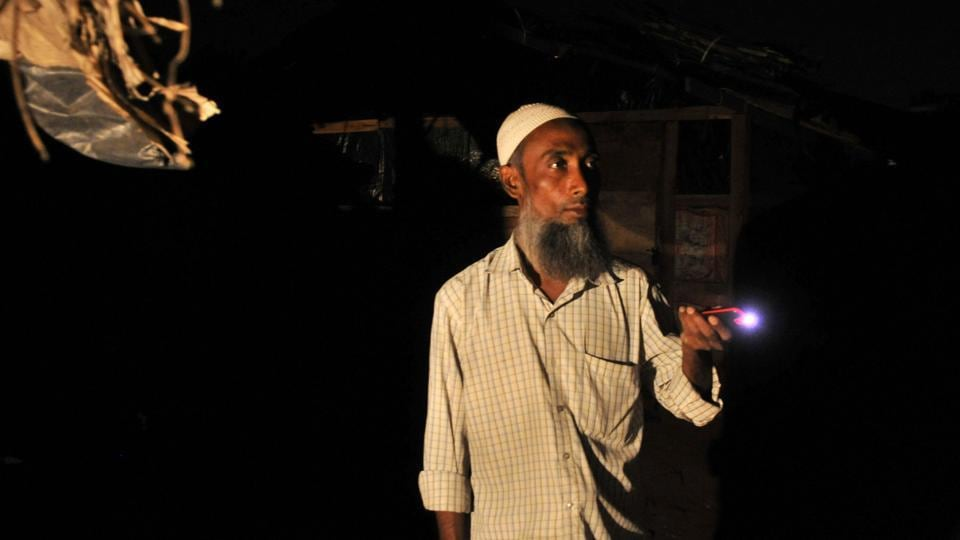 Kamal Hussain, a Rohingya Muslim, stands guard outside a settlement at night in Jammu.