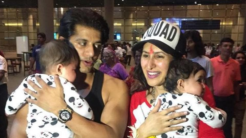 Karanvir Bohra and Teejay Sidgu with their daughters at the airport.
