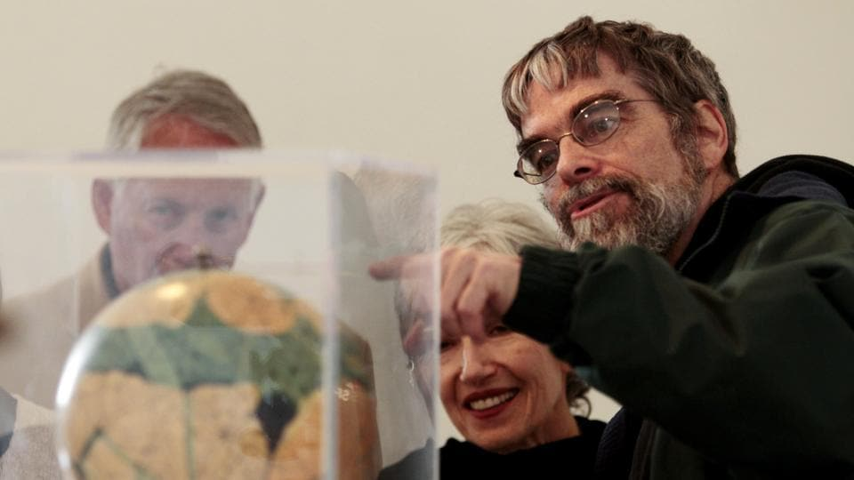 Jesuit Brother Guy Consolmagno, a Jesuit astronomer at the Vatican's Observatory, right, shows to visitors the Globe of planet Mars from the collection of the Specola Vaticana.