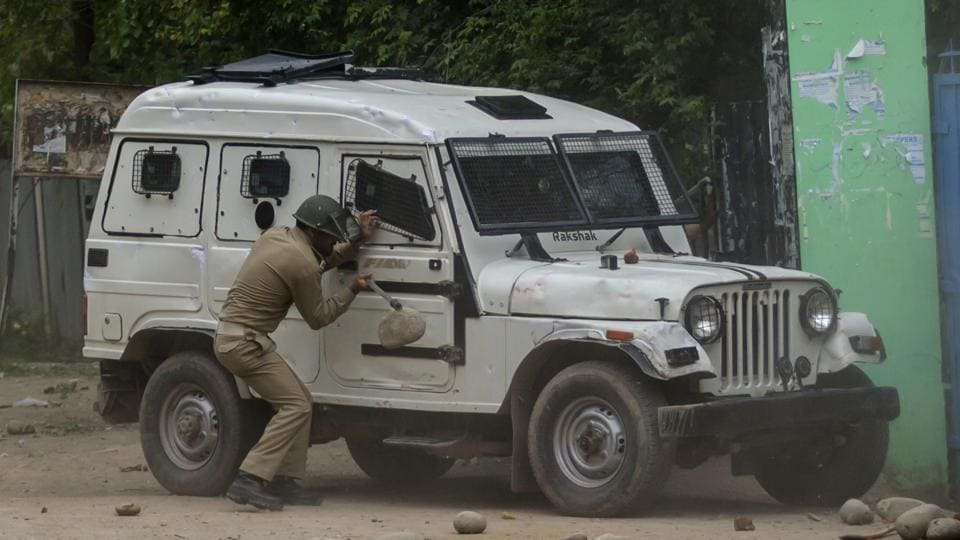 Representative Image: A policeman takes cover behind an armoured vehicle from rocks thrown at him by Kashmiri students during a protest in Budgam, about 20 kilometers southwest of Srinagar.