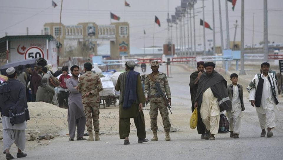 Pakistani paramilitary soldiers stand guard while people wait for the opening of the border crossing in Chaman, Pakistan.