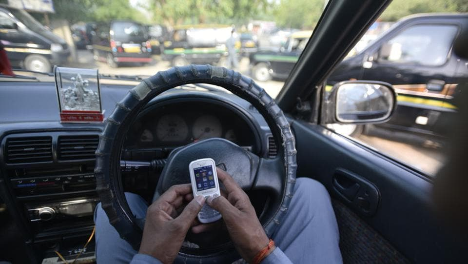 Sitting in his car at the parking lot waiting for passengers, Kapri spends his time checking messages or watching TV with his mates. (Ravi Choudhary/HT PHOTO)