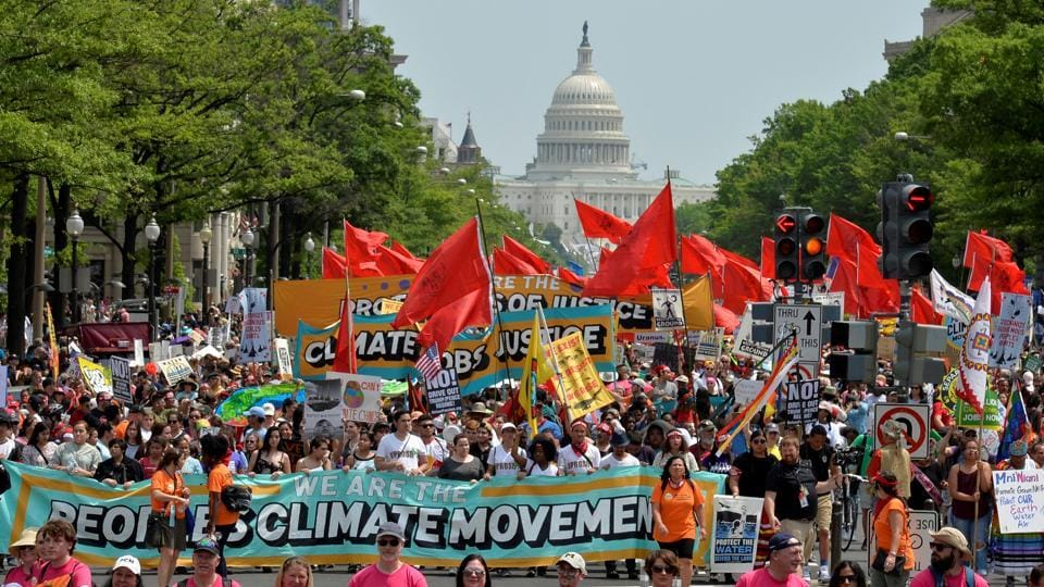 Demonstrators march down Pennsylvania Avenue during a People's Climate March, to protest US President Donald Trump's stance on the environment, in Washington DC on April 29.