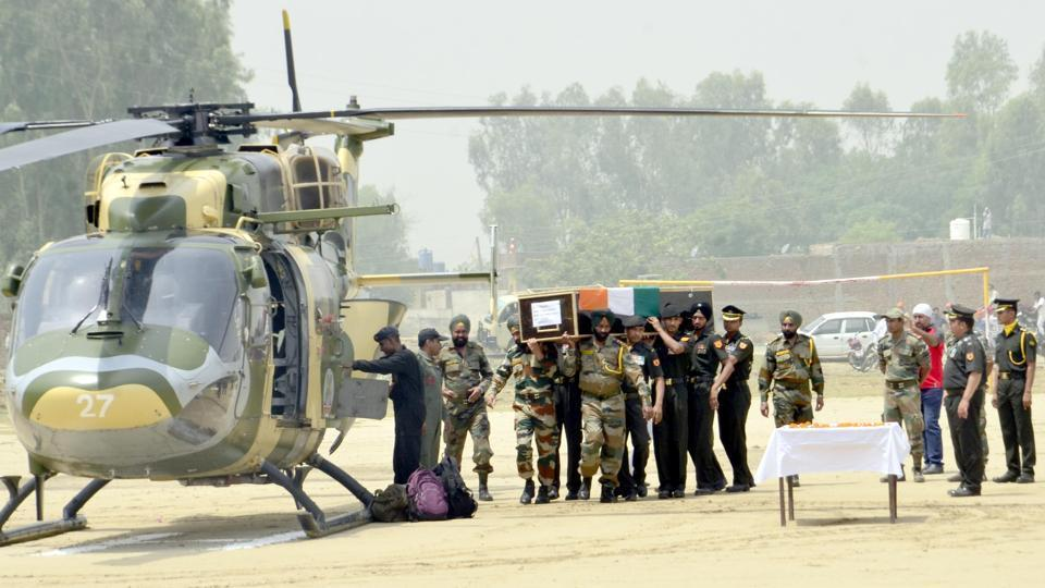 Indian Army personnel carry the coffin of Indian Army soldier Paramjeet Singh ahead of his funeral at Vein Pein village, some 45kms from Amritsar. The Indian army accused Pakistan of killing two of its soldiers and mutilating their bodies in an 'unprovoked' rocket and mortar attack along the border on May 1.