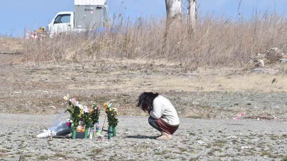 A woman prays for victims of the 2011 quake-tsunami disaster in Fukushima prefecture.