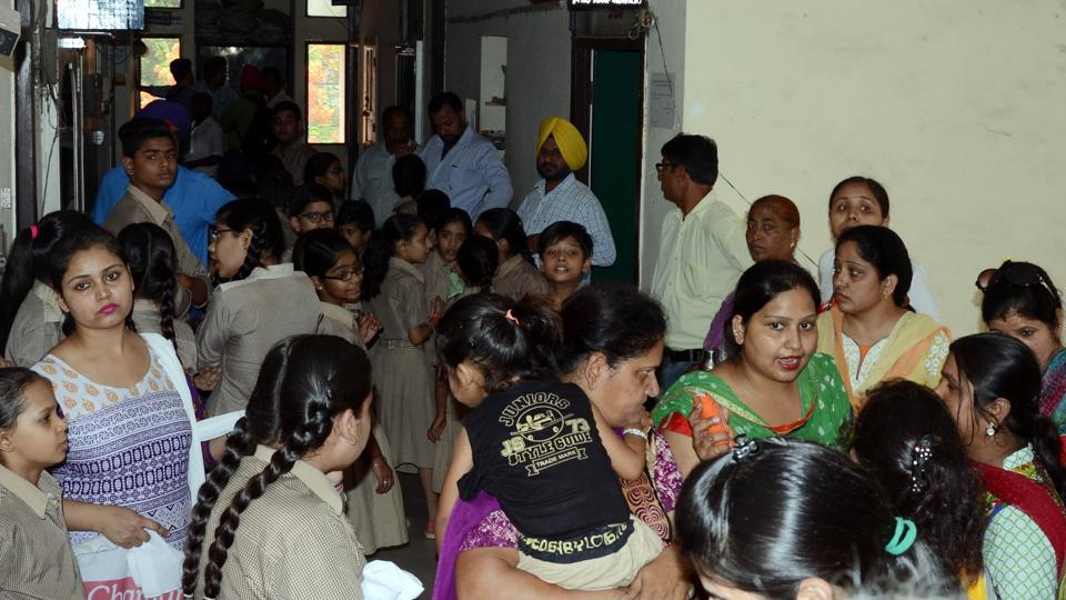 Parents along with their wards waiting outside the DEO's office in Ludhiana on Monday.