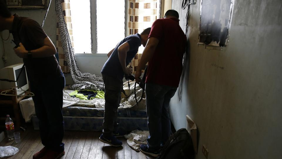 In this April 20, 2017, photo, investigators check a room in the home of suspected child webcam cybersex operator, David Timothy Deakin, from Peoria, Ill., during a raid in Mabalacat, Philippines.