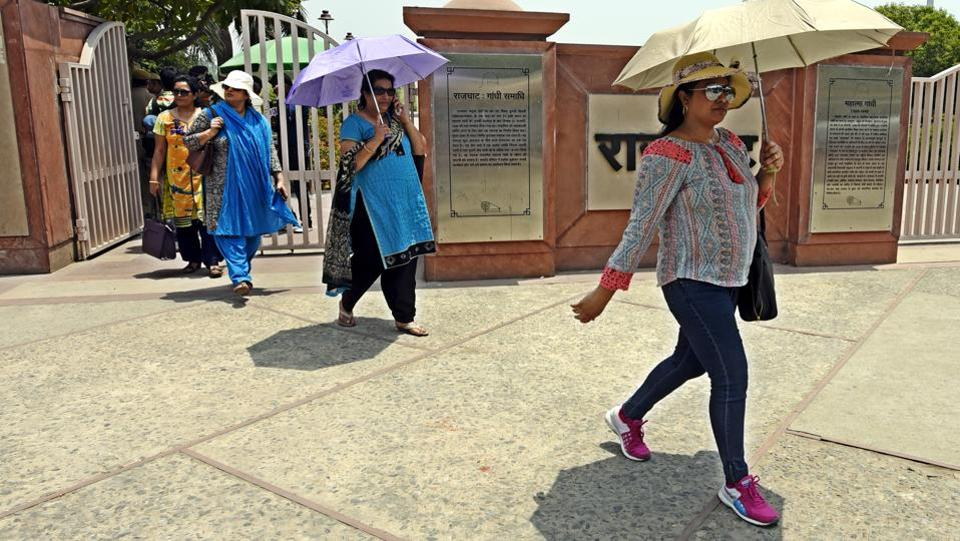 People cover themselves using umbrellas as scorching heat made a comeback over NCR, with mercury touching the 43 degree mark  yesterday.  (Sonu Mehta/HT PHOTO)