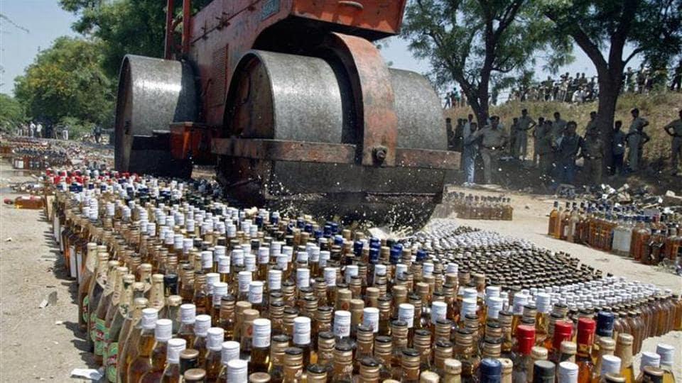 A roller crushes liquor bottles.