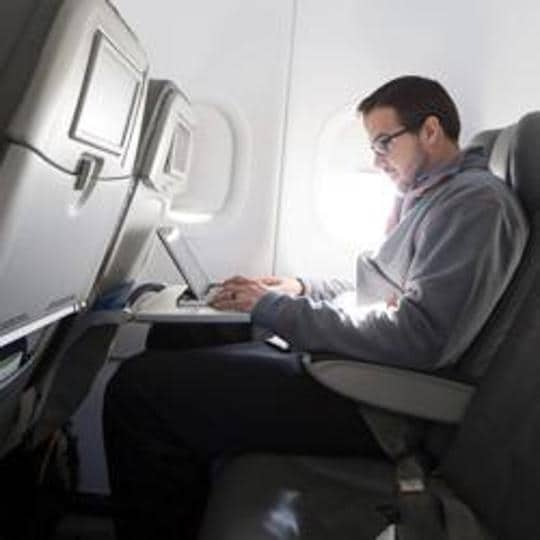 A man uses his laptop to test a new high speed inflight Internet service named Fli-Fi while on a special JetBlue media flight out of John F Kennedy International Airport in New York in this December 11, 2013 file picture.