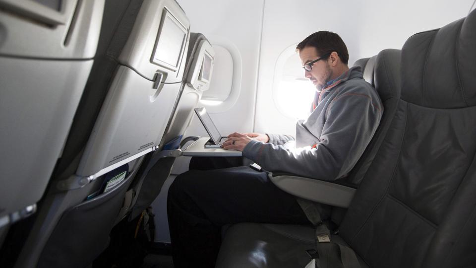 A man uses his laptop on a flight out of John F Kennedy International Airport in New York.