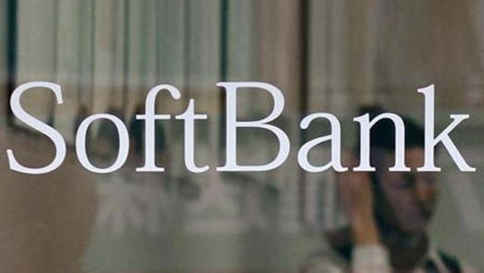 An employee works behind a logo of Softbank Corp at its branch in Tokyo.