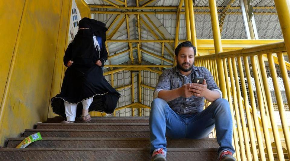 """A Kashmiri man browses the internet on his mobile phone on a footbridge in Srinagar. A statement released and published by the UN high commissioner for human rights said the social media gag was a """"collective punishment"""" that didn't meet the international standards for limiting free speech."""