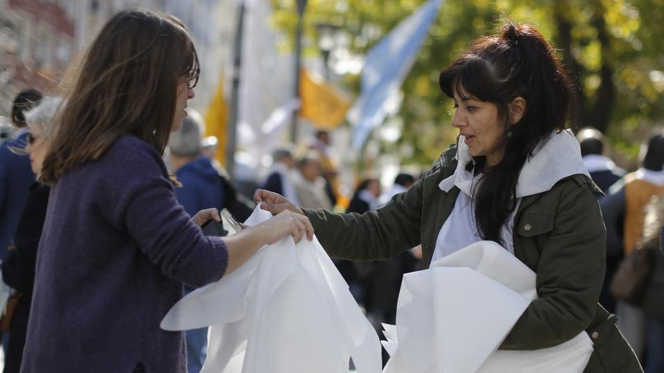 An activist, right, hands out handkerchiefs resembling the famous one used by the Mothers of Plaza de Mayo human rights group outside the Justice Palace in Buenos Aires. Official estimates say about 6,000 people were killed or disappeared during the dictatorship, but human rights activists believe the real number was as high as 30,000. (Victor R. Caivano/AP)