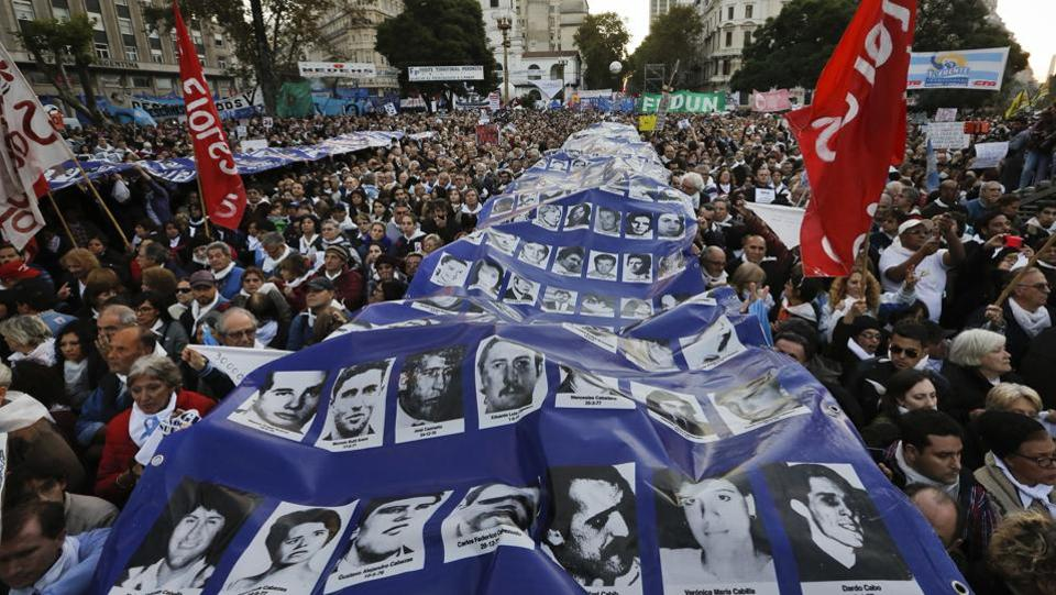 People hold a banner with photos of persons killed during Argentina's 1976-1983 dictatorship. Activists had warned that the ruling could set a precedent leading to the early release of other abusers. (Victor R. Caivano/AP)
