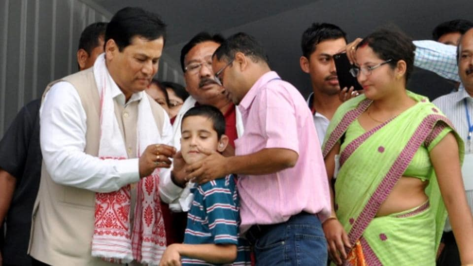 Assam Chief Minister Sarbananda Sonowal (L) distributes free aids and assistive devices to specially abled people at Amguri in Sivasagar on Wednesday.