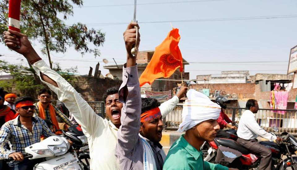 Hindu Yuva Vahini vigilante members participate in a rally in the city of Unnao, April 5.  Is it patriotic for vigilantes who in a show of patriotism for the sacred cow, insult, beleaguer and not hesitate to kill ordinary folk? Vigilantes do it to protect their misplaced cultural identity.