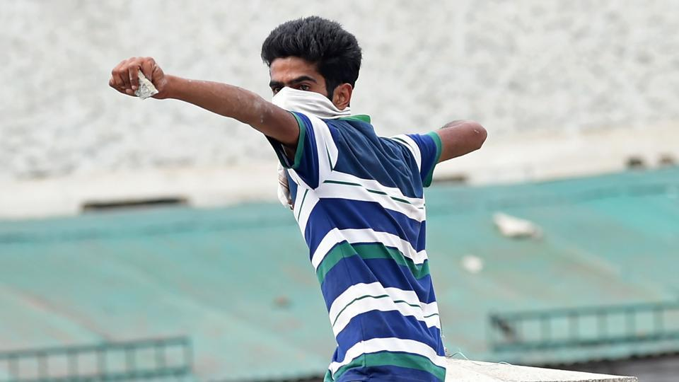 A Kashmiri student throws a stone during clashes between Kashmiri students and government forces in Srinagar's Lal Chowk.