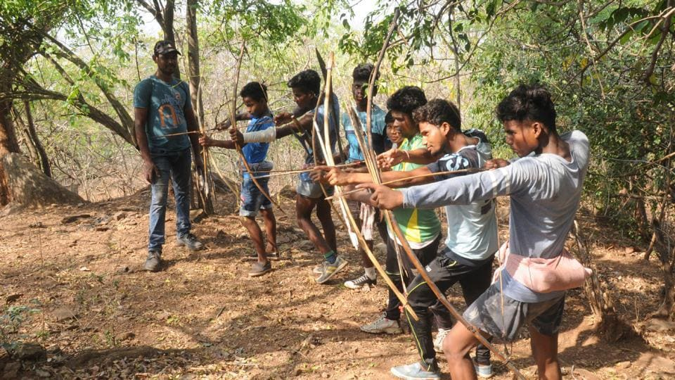 Tribals aiming on wild animals with their traditional weapons during