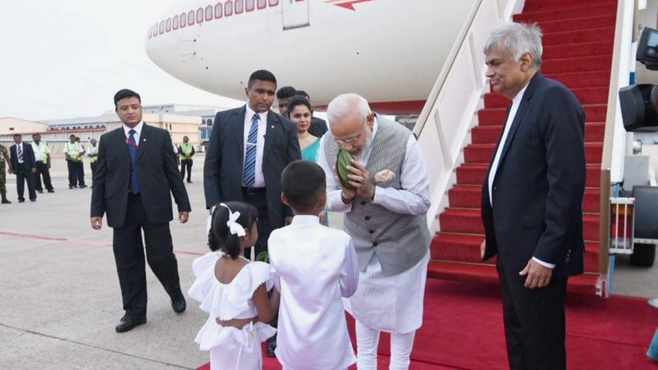Prime Minister Narendra Modi is greeted by children as he arrives at Bandaranaike International Airport in Colombo. Sri Lankan Prime Minister Ranil Wickremesinghe looks on.